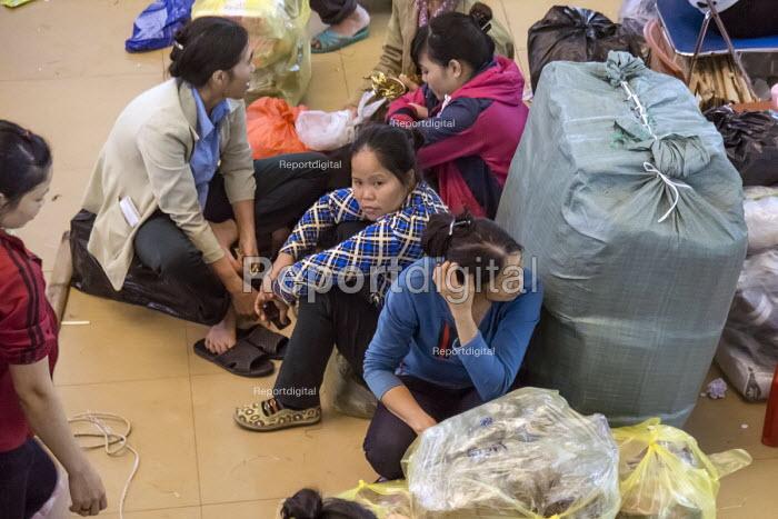 Shopworkers waiting with bundles of cloth, Dong Xuan Market, Hanoi, Vietnam - David Bacon - 2015-12-09