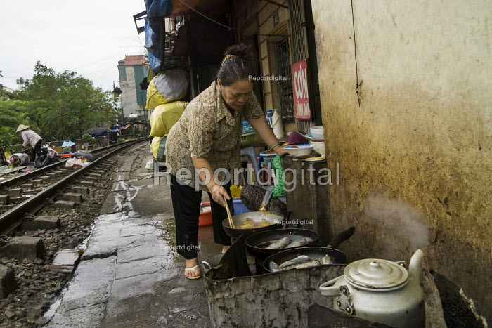 Homes next to the railway tracks, Hanoi, Vietnam. Cook preparing food for her small restaurant - David Bacon - 2015-12-09