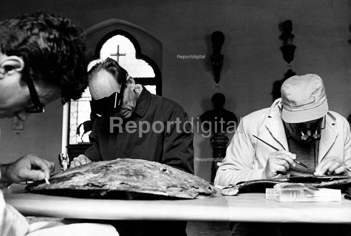 Florence Floods, Italy, 1966 in which 100 died and many cultural artefacts, books, paintings and sculptures were damaged. It was the worst flood for five hundred years. An American team of restorers repairing a 16th Century Venetian shield in the Museo Bargello. From left to right: Constantin Tsausis, Morton C Bradley & William J Young. - Romano Cagnoni - 1966-11-11