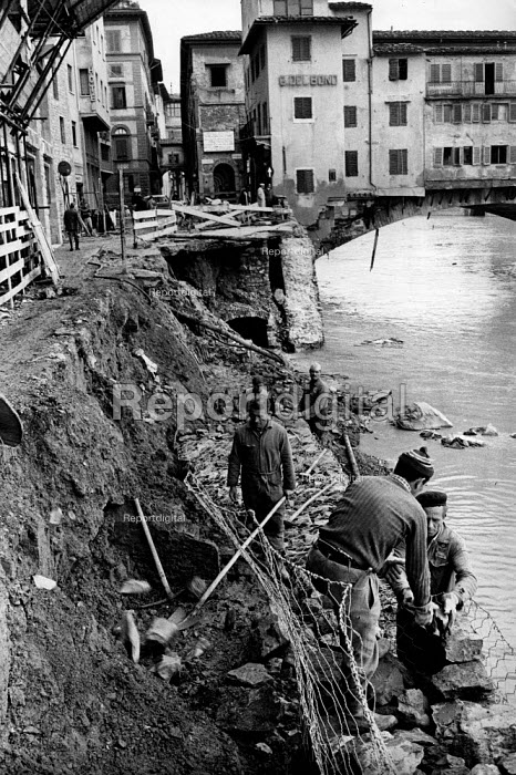 Florence Floods, Italy, 1966 in which 100 died and many cultural artefacts, books, paintings and sculptures were damaged. It was the worst flood for five hundred years. Workers repairing the embankment of the River Arno, with the famous Ponte Vecchio on the right. - Romano Cagnoni - 1966-11-14