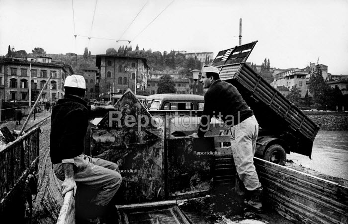 Florence Floods, Italy, 1966 in which 100 died and many cultural artefacts, books, paintings and sculptures were damaged. It was the worst flood for five hundred years. Damaged paintings on the back of a truck en route from the Uffizi Gallery to the Palazzo Pitti Gallery. On the right, army lorries unload mud and rubbish into the River Arno. - Romano Cagnoni - 1966-11-11