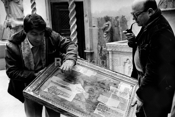 Florence Floods, Italy, 1966 in which 100 died and many cultural artefacts, books, paintings and sculptures were damaged. It was the worst flood for five hundred years. In the Bardini Museum, the Director, with pipe, and a restorer discuss what to do with a Cranach painting, the damaged parts of which are covered with tissue paper to avoid further loss of colour. - Romano Cagnoni - 1966-11-11