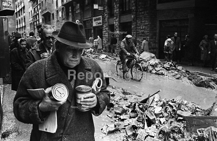 Man with tins of food from a distribution centre, Florence Floods, Italy, 1966. The floods in Florence in early November 1966 were the worst in over five hundred years and resulted in the loss of over 100 Florentine lives as well as damage to thousands of cultural artefacts, including ancients books, paintings and sculptures. Florentines returning from a food distribution centre on a street behind the Palazzo Vecchio. - Romano Cagnoni - 1966-11-14