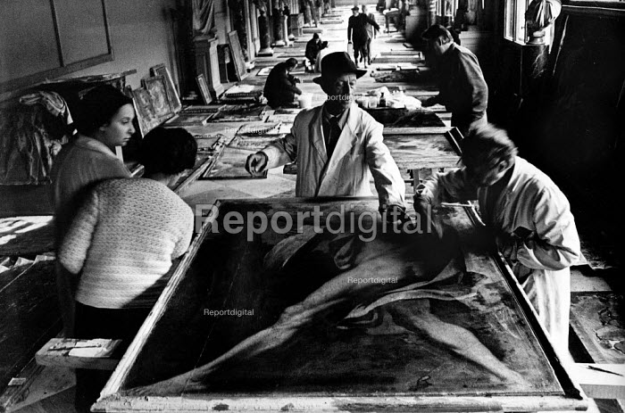 Florence Floods, Italy, 1966 in which 100 died and many cultural artefacts, books, paintings and sculptures were damaged. It was the worst flood for five hundred years. On the upper floors of the Uffizi gallery, a full process of restoration of the damaged artwork gets underway. Hundreds of paintings are piled on the floor and up against the walls. - Romano Cagnoni - 1966-11-11