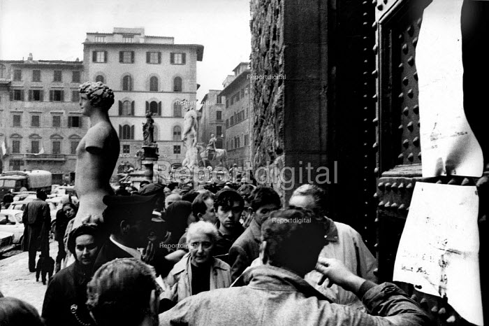 Florence Floods, Italy, 1966 in which 100 died and many cultural artefacts, books, paintings and sculptures were damaged. It was the worst flood for five hundred years. A long queue on the Piazza della Signoria, outside the Palazzo Vecchio, waiting for the municipal distribution of food for those in dire need. - Romano Cagnoni - 1966-11-11