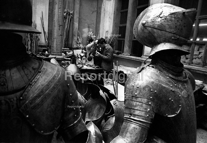 Florence Floods, Italy, 1966 in which 100 died and many cultural artefacts, books, paintings and sculptures were damaged. It was the worst flood for five hundred years. Suits and armour taken from the Bargello Museum to the courtyard of the Uffizi Gallery. Student volunteers dry and oil each piece thoroughly to prevent the rust which can grow very quickly on the armour. - Romano Cagnoni - 1966-11-11
