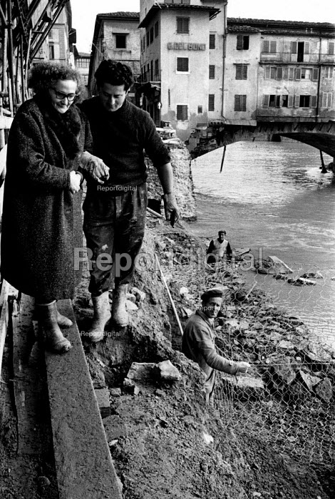 Florence Floods, Italy, 1966 in which 100 died and many cultural artefacts, books, paintings and sculptures were damaged. It was the worst flood for five hundred years. Workers helping a resident across duck boards as repairs are made to the embankment of the River Arno, with the famous Ponte Vecchio on the right. - Romano Cagnoni - 1966-11-14