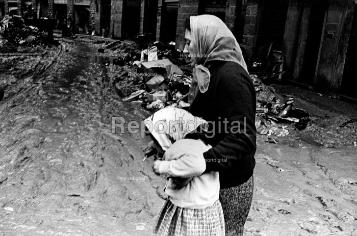 Florence Floods, Italy, 1966 in which 100 died and many cultural artefacts, books, paintings and sculptures were damaged. It was the worst flood for five hundred years. In a working class quarter near the banks of the River Arno, a mother carrying her daughter whilst wading through slippery mud. - Romano Cagnoni - 1966-11-14