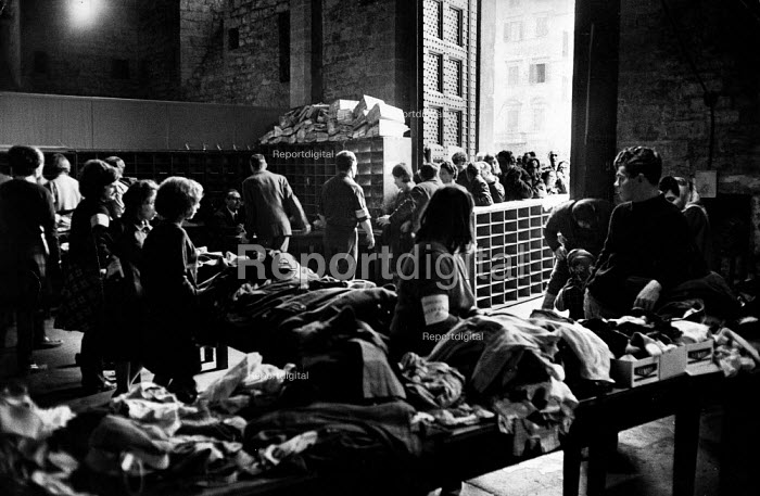 Florence Floods, Italy, 1966 in which 100 died and many cultural artefacts, books, paintings and sculptures were damaged. It was the worst flood for five hundred years. Distributing clothing to local citizens in the Palazzo Vecchio as part of the flood relief programme. - Romano Cagnoni - 1966-11-11