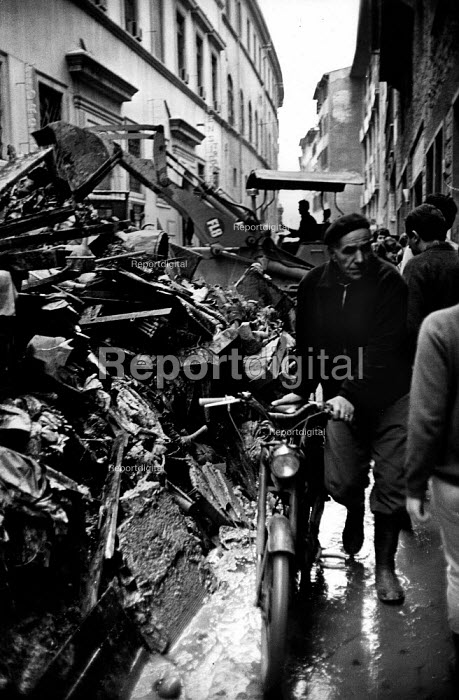 Florence Floods, Italy, 1966 in which 100 died and many cultural artefacts, books, paintings and sculptures were damaged. It was the worst flood for five hundred years. Digger piling rubbish on one side of the muddy treet so people can pass by. - Romano Cagnoni - 1966-11-11