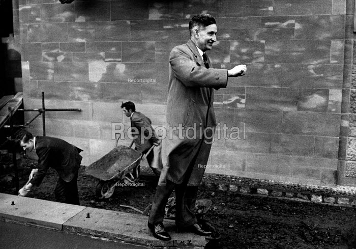 Rebuilding of Coventry Cathedral being completed 1962 more than two decades after the bomb damage World War Two. Mr Stocks, the builder's agent, directing workers levelling the ground outside the Cathedral walls. - Alex Low - 1962-03-03