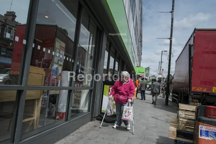 Woman with crutches and shopping bags outside Cricklewood Co-op store, London. - Philip Wolmuth - 2016-05-20