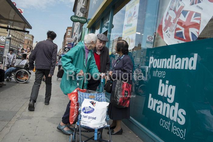Elderly shoppers chat outside a Poundland store, Kilburn, London. - Philip Wolmuth - 2016-05-27