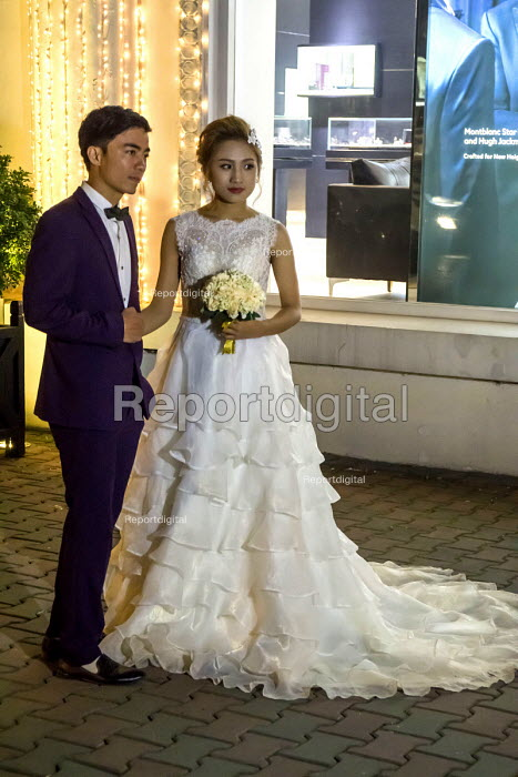 Hanoi, Vietnam, bride and groom having their picture taken at night by Hotel Metropole, a custom for women about to get married - David Bacon - 2016-01-05
