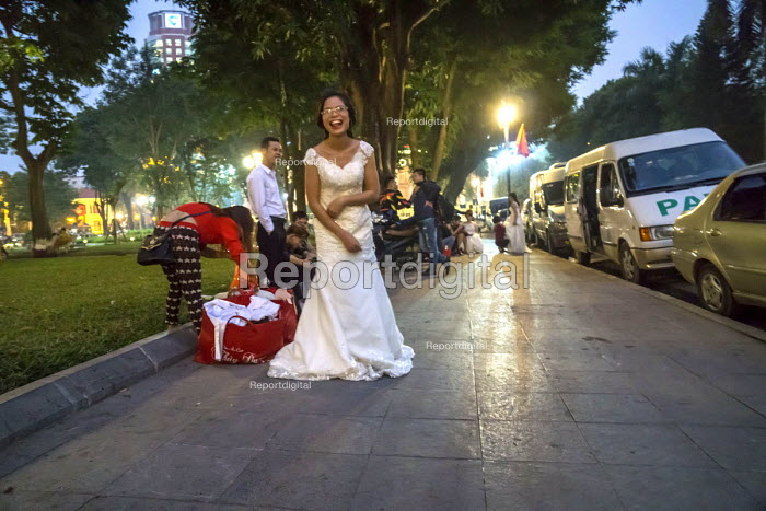 Hanoi, Vietnam bride getting ready for her wedding picture to be taken on a steet beside Ly Thai Tho Park, in a custom for women about to get married. - David Bacon - 2016-01-05