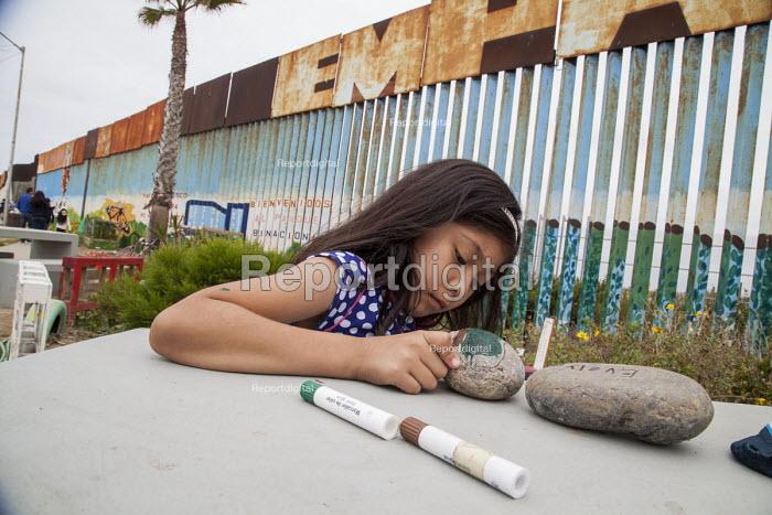 Tijuana Mexico USA border. Children writing the names of family members on stones. Every Sunday Mexicans greet family members on the USA side through the border fence, Parque de Amistad, or Friendship Park, Tijuana where the wall runs into the Pacific Ocean - David Bacon - 2016-05-29