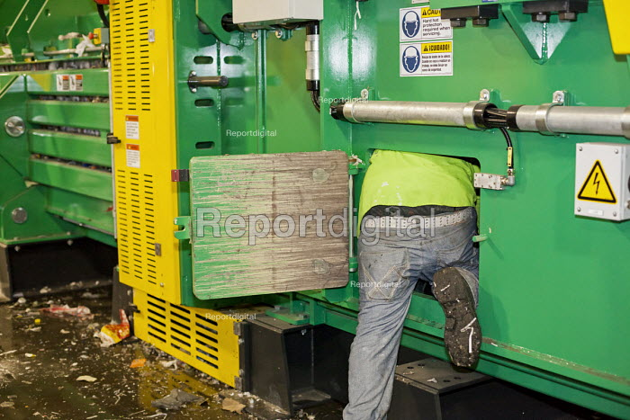 Southfield, Michigan, ReCommunity materials recovery facility, where recyclable materials are sorted and baled. A worker trying to fix a jammed baling machine - Jim West - 2016-03-31