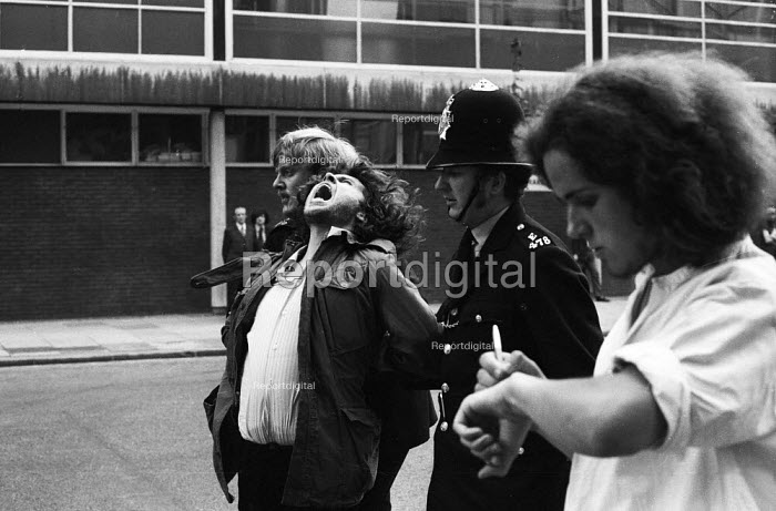 National Front demonstration to Conway Hall in Red Lion Square and counter demonstration led by Liberation, London, 1974. An anti-Fascist protestor is placed in a painful arm lock and arrested by police his friend writes down the police numbers on his hand to identify the arresting officers. In the riot in the Square between police and demonstrators, Warwick student, Kevin Gately was killed the first fatality of rioting on British soil in fifty years. - Mike Tomlinson - 1974-06-15
