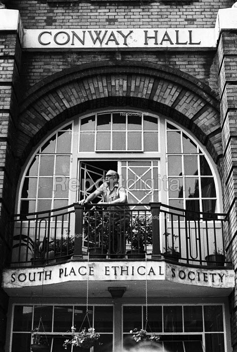 National Front demonstration to Conway Hall in Red Lion Square and counter demonstration led by Liberation, London, 1974. A member of staff looks down on the protestors from the balcony of Conway Hall facing Red Lion Square. In the riot in the Square that followed clashes between police and demonstrators, Warwick student, Kevin Gately was killed; the first fatality of rioting on British soil in fifty years. - Mike Tomlinson - 1974-06-15