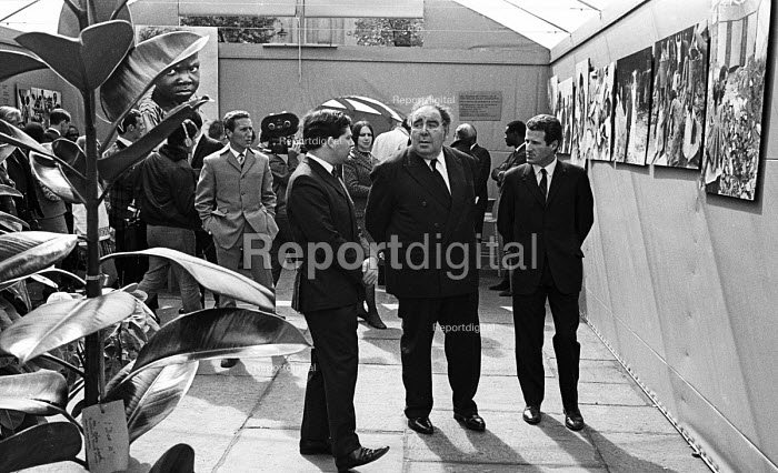 Opening of a photographic exhibition by Romano Cagnoni of Report on Biafra during the Nigerian Civil War, London, 1969. The exhibition was staged in a tent in Trafalgar Square and sponsored by The Spectator Magazine. Left to Right: Nigel Lawson, Editor of The Spectator, Lord Goodman and photographer, Romano Cagnoni. Behind Lawson to his left, is writer, Frederick Forsyth who reported extensively on the war. - Patrick Eagar - 1969-10-10