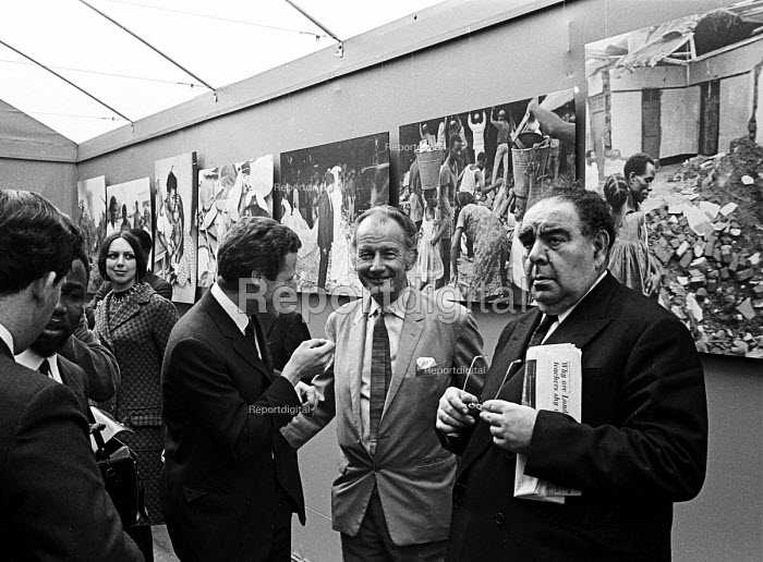 Opening of a photographic exhibition by Romano Cagnoni of Report on Biafra during the Nigerian Civil War, London, 1969. The exhibition was staged in a tent in Trafalgar Square and sponsored by The Spectator Magazine. Left to Right: photographer, Romano Cagnoni, journalist, James Cameron & Lord Goodman. - Patrick Eagar - 1969-10-10