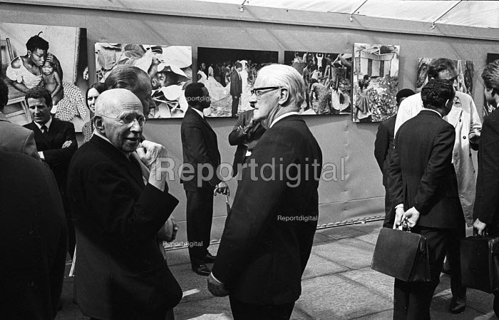 Opening of a photographic exhibition by Romano Cagnoni of Report on Biafra during the Nigerian Civil War, London, 1969. The exhibition was staged in a tent in Trafalgar Square and sponsored by The Spectator Magazine. Report Founder & Secretary, Simon Guttmann, left, in conversation with Lord Fenner Brockway. Photographer, Romano Cagnoni is behind Guttmann to his left. - Patrick Eagar - 1969-10-10
