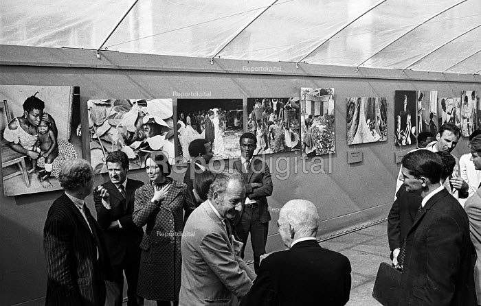 Opening of a photographic exhibition by Romano Cagnoni of Report on Biafra during the Nigerian Civil War, London, 1969. The exhibition was staged in a tent in Trafalgar Square and sponsored by The Spectator Magazine. Photographer, Romano Cagnoni, second left, on his right, artist Berenice Sydney. In foreground, journalist, James Cameron is in conversation with Report Founder & Secretary, Simon Guttmann, back to camera. - Patrick Eagar - 1969-10-10
