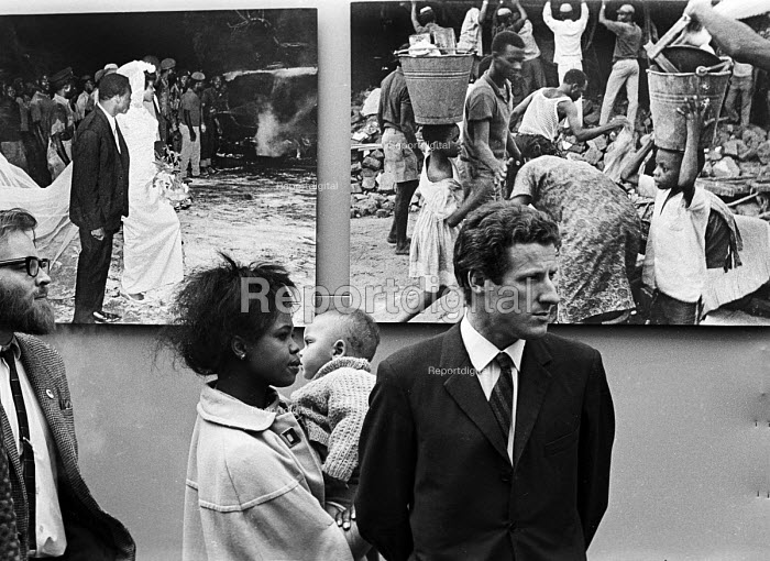 Opening of a photographic exhibition by Romano Cagnoni of Report on Biafra during the Nigerian Civil War, London, 1969. The exhibition was staged in a tent in Trafalgar Square and sponsored by The Spectator Magazine. Photographer, Romano Cagnoni, in front of two of his photographs from the exhibition - Patrick Eagar - 1969-10-10