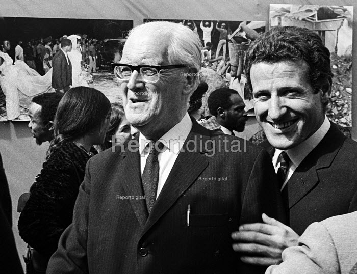 Opening of a photographic exhibition by Romano Cagnoni on Biafra during the Nigerian Civil War, London, 1969. The exhibition was staged in a tent in Trafalgar Square and sponsored by The Spectator Magazine. Photographer, Romano Cagnoni, on right, with Lord Fenner Brockway. - Patrick Eagar - 1969-10-10