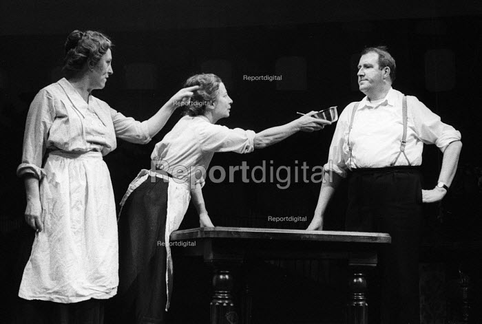 Better Times written by Barrie Keeffe, staged at Theatre Royal Stratford East, London 1985. The play tells the story of the 1921 Poplar Rates Revolt. Councillor Julia Scurr, played by Kate Williams and Nellie Cressel, played by Jean Hart, offer food to The Constable, played by Gordon Kaye; food considered not fit for animals but still given to Poplar's poor. - Stefano Cagnoni - 1985-01-30