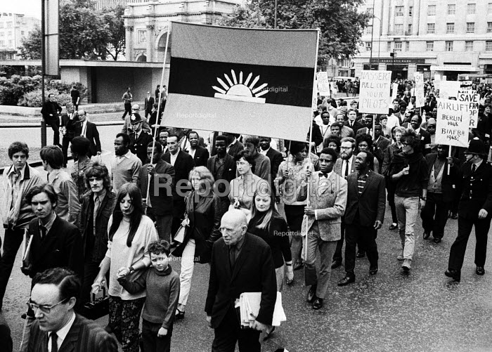 Supporters of Biafra protest against the British Government supplying arms to Nigeria during the Nigerian Civil War, London, 1968. Simon Guttmann, newspapers under his arm. - Romano Cagnoni - 1968-06-23