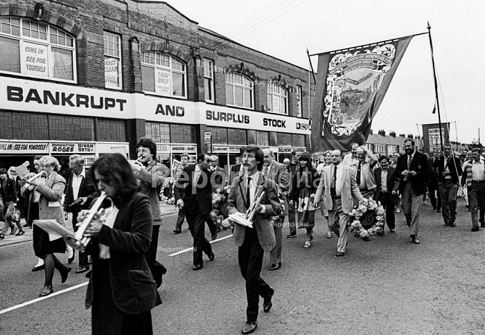 """Durham Miners Gala, 1983. Miners and their families march on the 100th Anniversary of the Durham Miners Gala or """"Big Meeting"""". Passing a local shop selling bankrupt and surplus stock. - Stefano Cagnoni - 1983-07-16"""