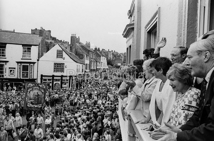 """Durham Miners Gala, 1983. Miners and their families march on the 100th Anniversary of the Durham Miners Gala or """"Big Meeting"""". Labour Party leaders, including Tony Benn & Neil Kinnock, wave to the procession from the balcony of The County Hotel - Stefano Cagnoni - 1983-07-16"""