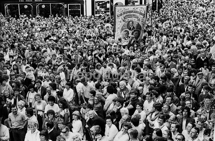 "Durham Miners Gala, 1983. Miners and their families march on the 100th Anniversary of the Durham Miners Gala or ""Big Meeting"". Huge crowds line the narrow streets of Durham with the Craghead Lodge Banner in their midst. - Stefano Cagnoni - 1983-07-16"