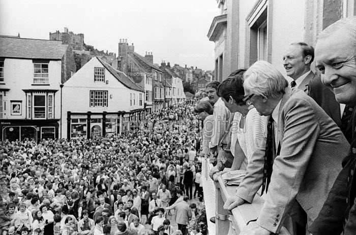 """Durham Miners Gala, 1983. Miners and their families march on the 100th Anniversary of the Durham Miners Gala or """"Big Meeting"""". Labour Party leaders, Michael Foot, Neil KInnock and Tony Benn watch the procession from the balcony of The County Hotel. - Stefano Cagnoni - 1983-07-16"""