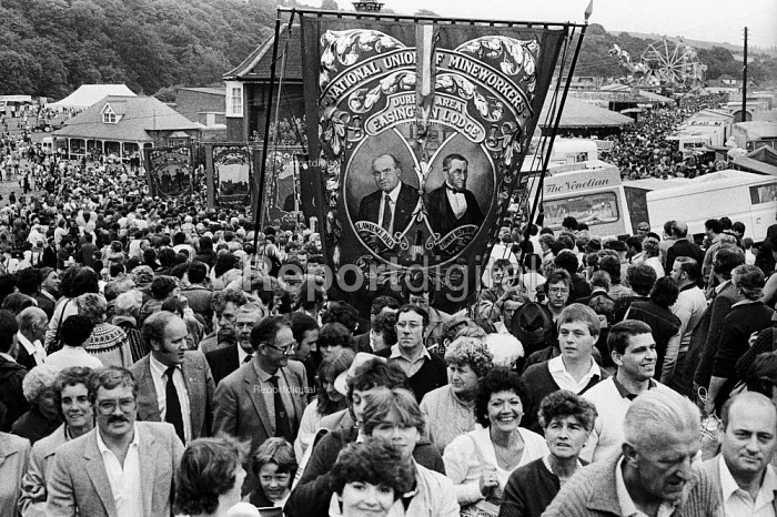 "Durham Miners Gala, 1983. Miners and their families march on the 100th Anniversary of the Durham Miners Gala or ""Big Meeting"". The Easington Lodge banner leads the way to the fairground held on the Durham Racecourse. - Stefano Cagnoni - 1983-07-16"
