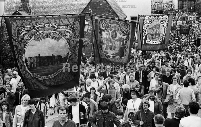 "Durham Miners Gala, 1983. Miners and their families march on the 100th Anniversary of the Durham Miners Gala or ""Big Meeting"".The Pit banners of Witton Lodge, Sacriston, of Langley Park Lodge, and of Hobson Lodge are carried back through the streets of Durham at the end of the procession. - Stefano Cagnoni - 1983-07-16"