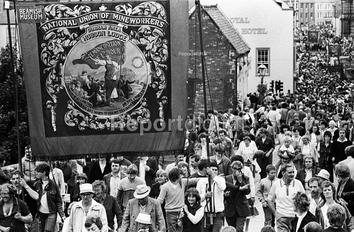 """Durham Miners Gala, 1983. Miners and their families march on the 100th Anniversary of the Durham Miners Gala or """"Big Meeting"""". The Hobson Lodge pit banner is carried back through the streets at the end of the procession. - Stefano Cagnoni - 1983-07-16"""