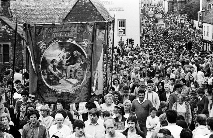"Durham Miners Gala, 1983. Miners and their families march on the 100th Anniversary of the Durham Miners Gala or ""Big Meeting"". The Hedleyhope Lodge banner, bearing the time honoured, Socialist slogan Unity is Strength, is carried back through the streets at the end of the procession. - Stefano Cagnoni - 1983-07-16"