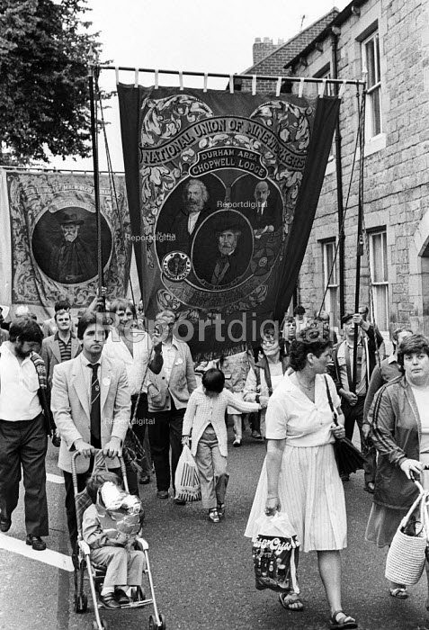 """Durham Miners Gala, 1983. Miners and their families march on the 100th Anniversary of the Durham Miners Gala or """"Big Meeting"""". The Chopwell Lodge pit banner, bearing the portraits of Karl Marx, Lenin & Keir Hardie is carried through the streets of Durham - Stefano Cagnoni - 1983-07-16"""