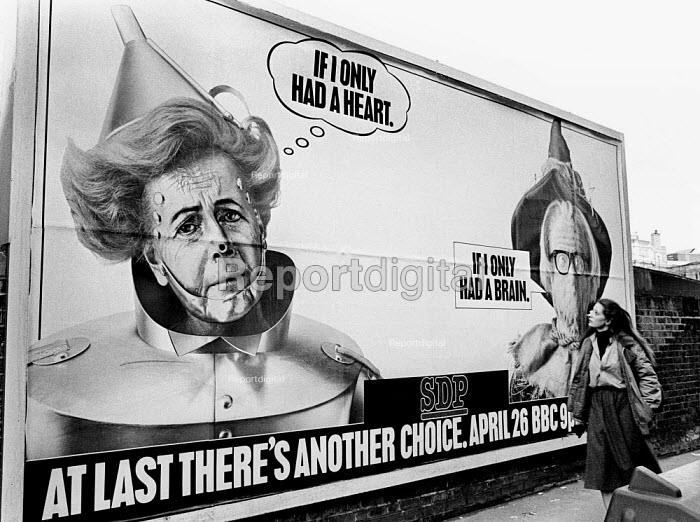 General Election Campaign 1983. Woman glances up at a billboard poster advertising an SDP Party Political Broadcast. Depicting Margaret Thatcher as The Tin Man and Michael Foot as The Scarecrow, characters from The Wizard of Oz, . The SDP split the Labour vote - Stefano Cagnoni - 1983-04-22