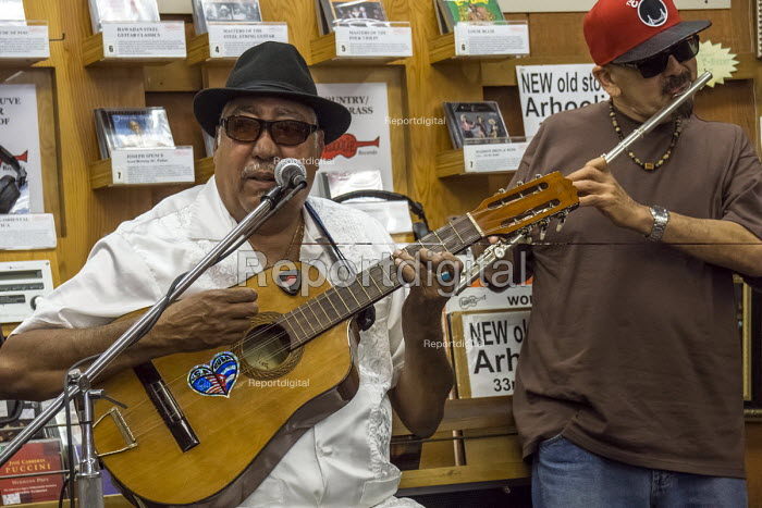 """El Cerrito, California, Cuban musician Heriberto """"Tito"""" Gonzalez, composer and band leader playing a tres with Ruben Hurtado, flautist and an impromptu group of Son cubano musicians, Down Home Music Store - David Bacon - 2016-06-26"""
