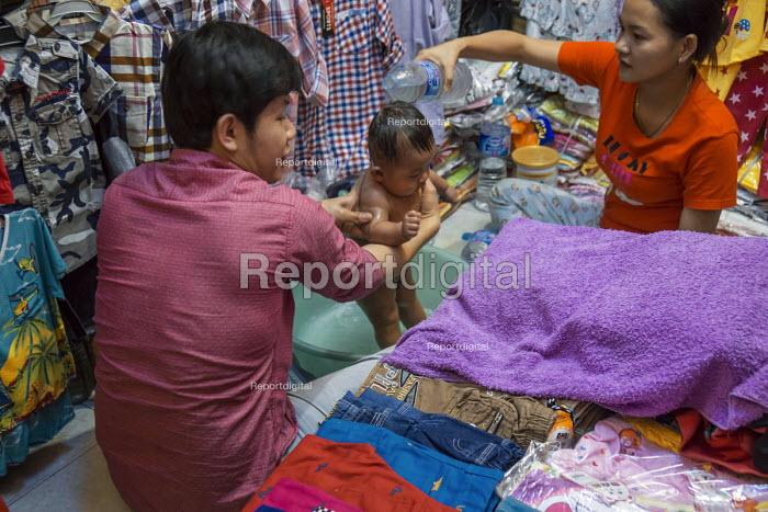 Battambang, Cambodia, stall holders give their baby a bath at the back of the shop - David Bacon - 2015-12-24