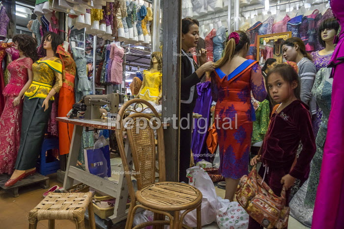 Battambang, Cambodia, woman trying on a dress in a stall in the Phsar Nath Market - David Bacon - 2015-12-24