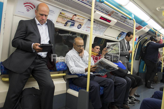 Passengers reading devices and Evening Standard newspaper on a London tube train - Philip Wolmuth - 2016-07-28