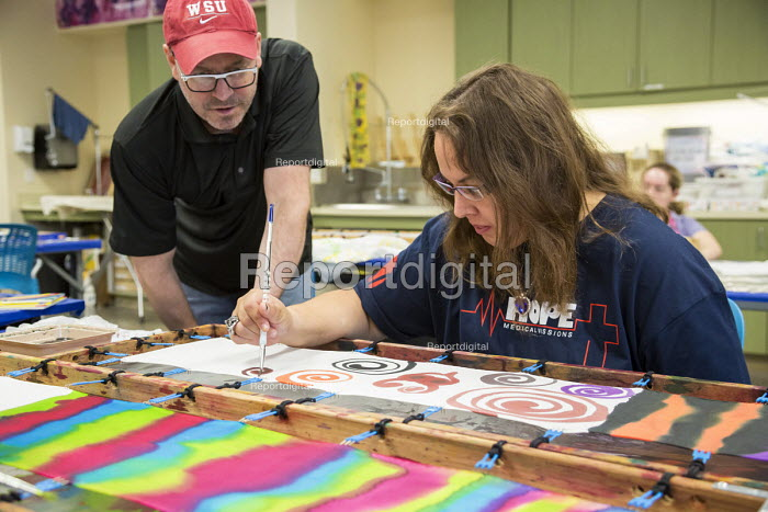Las Vegas, Nevada - An instructor helps a woman with an intellectual disability paint a silk scarf in the Fine Art Program run by the nonprofit Opportunity Village. The artists are paid a commission when their work is sold. - Jim West - 2016-06-30
