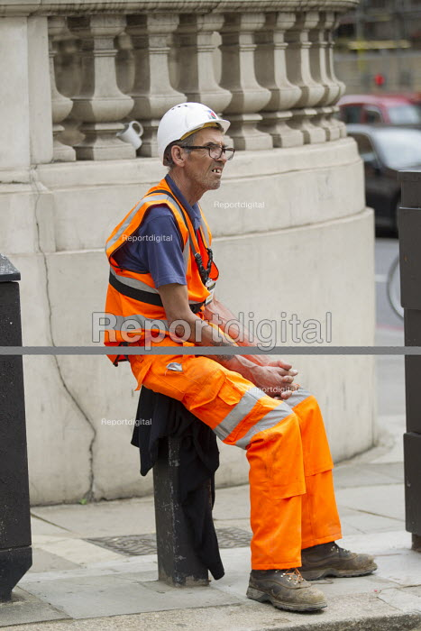 Construction worker with video badge having a break in the summer heat, Knightsbridge, London. VB-100 body worn video camera system is styled as an ID card holder worn around the neck - Jess Hurd - 2016-08-25