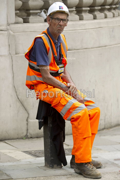Recording in progress. Construction worker with Edesix video badge having a break in the summer heat, Knightsbridge, London. VB-100 body worn video camera system is styled as an ID card holder worn around the neck - Jess Hurd - 2016-08-25