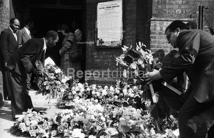 Mourners laying flowers at the funeral of Kelso Cochrane, St Michael and All Angels Church, Ladbroke Grove, West London, 1959. Kelso Cochrane, an Antiguan immigrant, was stabbed by 3 white youths, thought to be linked to the Oswald Mosley Union Movement fascist presence in the area. His unsolved murder, following on from the Notting Hill race riots a year earlier, led to the British Government holding an enquiry into race relations - Alan Vines - 1959-06-06