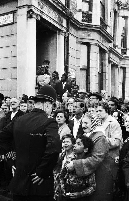 Around 1200 local people watching the funeral procession of Kelso Cochrane at the St Michael and All Angels Church, Ladbroke Grove, west London, 1959. Kelso Cochrane, an Antiguan immigrant, was stabbed by 3 white youths, thought to be linked to the Oswald Mosley Union Movement fascist presence in the area. His unsolved murder, following on from the Notting Hill race riots a year earlier, led to the British Government holding an enquiry into race relations - Alan Vines - 1959-06-06
